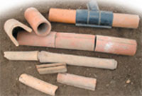 Figure 19.1 Drainage pipes. Modern clay pipes shown in the centre are butted up close together. An older method is shown below it and modern plastic piping is shown above. In the top left is a view of the modern clay pipe alongside the old 'horse shoe' tile (it would have sat on a 'mug plate' to prevent moving water washing away soil) and at the bottom are smaller examples of this type of old pipe
